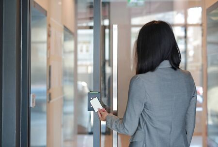 Young officer woman holding a key card to lock and unlock door for access entry. Door access control. Back view.