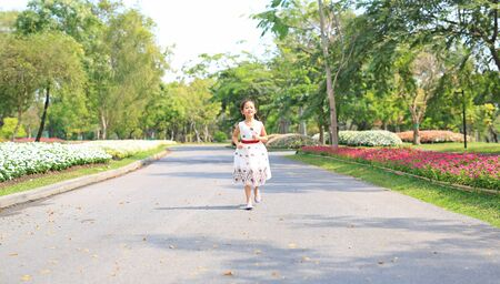Cheerful asian little girl in white dress running on road in garden. Фото со стока