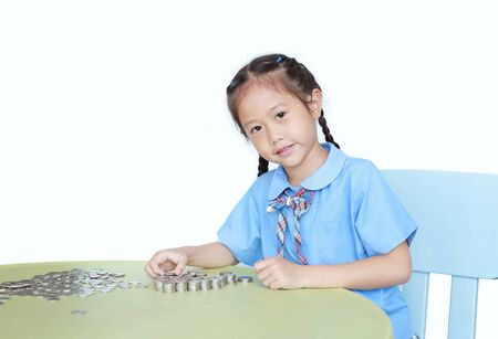 Asian little girl in school uniform sitting on table with stack of coins for saving over white background. Kid counting money. Schoolgirl with Money saving for the future concept.