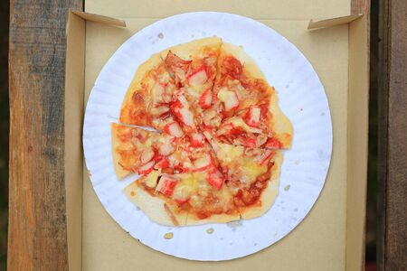 Close-up delicious homemade Pizza in cardboard paper box on wooden table. Top view. Фото со стока