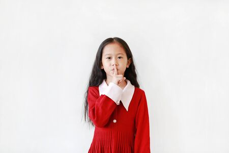 Beautiful Asian little girl make expression a Keep Quiet Gesture isolated on white background. Portrait of Kid holding index finger on lips to keep silence.