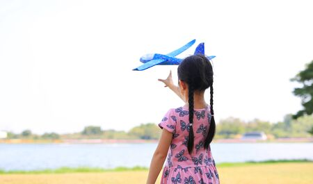 Asian little kid girl throwing a toy plane to flying on air in the nature garden. Rear view.