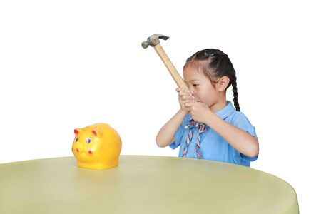 Little child girl in school uniform taking hammer trying to broke piggy bank isolated on white background at table. Schoolgirl with Money saving concept.