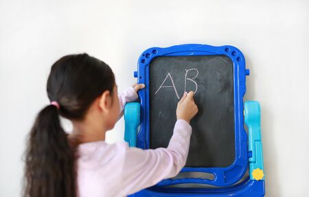 Little Asian child girl writing on blank black board over white background. Education concept. Rear view. Фото со стока