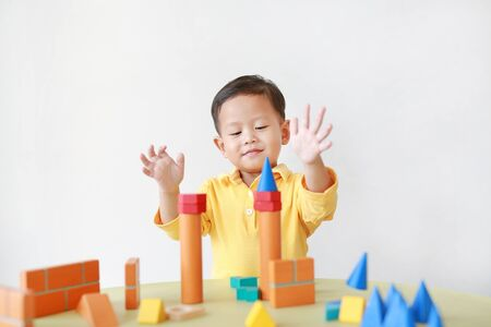 Cheerful asian little baby boy playing a colorful wood block toy on table over white background.
