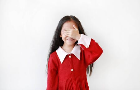 Portrait of smiling little Asian child girl in scarlet red dress covering eyes with hand isolated over white background.