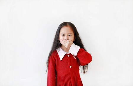 Portrait asian little girl in scarlet dress expression covering mouth with hand isolated on white background. Kid have a Secret concept.
