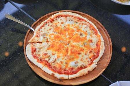 Delicious pizza served on wood tray against on black table.