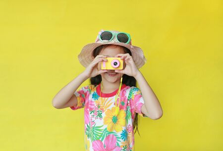 Asian little child girl wearing a floral pattern summer dress and hat with sunglasses taking photo by toy camera at you isolated on yellow background. Holiday and summer fashion concept. Фото со стока