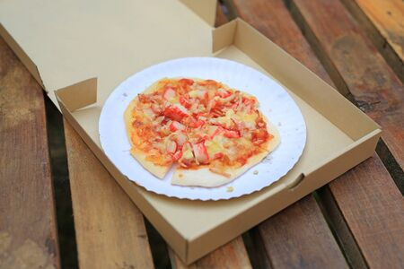 Delicious homemade Pizza in cardboard paper box on wooden table. Фото со стока