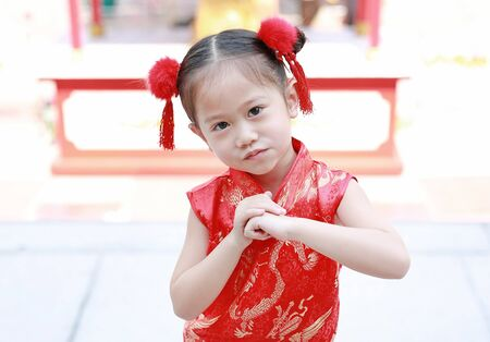 Little Asian girl wishing you a happy Chinese New Year at chinese temple in thailand.
