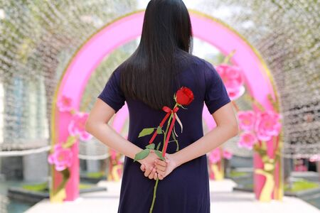 Retrato de mujer asiática escondiendo rosas rojas detrás de su espalda. Vista trasera.