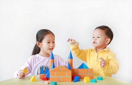 Asian little child girl and baby boy playing a colorful wood block toy on table over white background. Sister and her brother playing together.