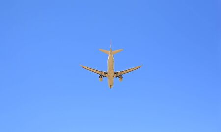 Commercial jet airplane flight on blue sky background. Seen from rear and below 免版税图像