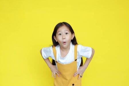 Funny face little child girl amazing expression isolated on yellow background. Asian kid with excited gesture 스톡 콘텐츠