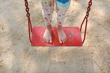 Feet of kid standing on red metal swing