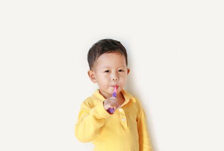 Portrait of little Asian baby boy brushing teeth on on white background.