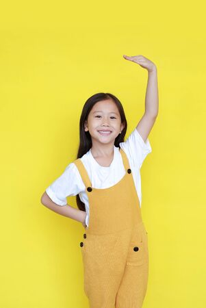 Little asian child girl measures the growth on yellow background. Kid estimate her height by hand with looking camera Standard-Bild