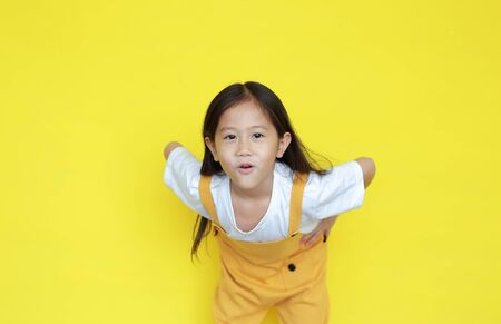 Adorable little child girl amazing expression isolated on yellow background. Asian kid with excited gesture. Stock Photo