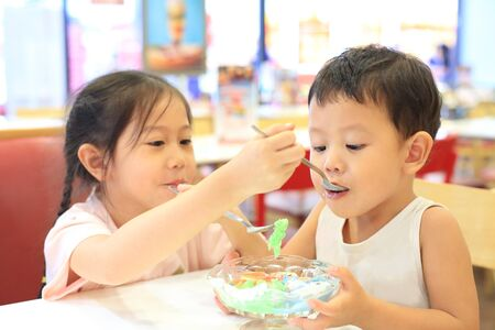 Asian sister and her little brother eating icecream together. Child girl feeding ice cream for baby boy in cafe.
