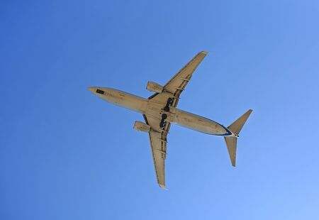 Commercial jet airplane flight on blue sky background. Seen from below.