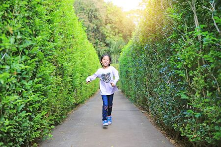 Asian child girl running in garden Maze. Kid playing in labyrinth for fun and entertainment.