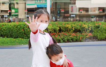 Covid-19 and air pollution stop concept. Asian little child girl and her brother wearing mask to protect coronavirus and pm2.5 dust with showing palm hand in public area outdoor. Focus at kid hand.