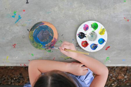 Asian little kid girl painting on earthenware dish. View on top. Stock fotó