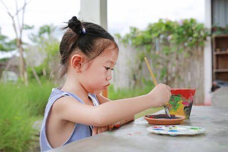 Asian kid girl paint on earthenware dish.