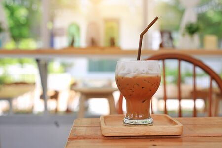 Iced coffee with milk on wooden table at cafe.