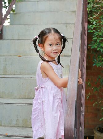 Cute little child girl walk up on stair railing. Pigtail girl looking at camera. Banque d'images - 143482560