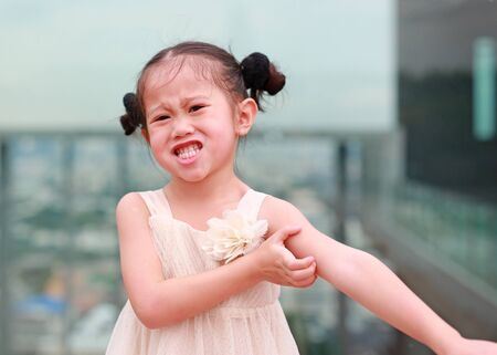 Funny face of little Asian girl scratch the itch with hand. Healthcare concept.
