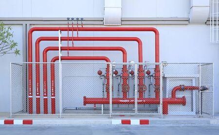 Red pipe of Fire Fighting systems in industrial zone in iron mesh fence. Water station in factory area zone.