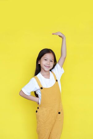Smiling asian little child girl measures growth by hand isolated over yellow background. Kid estimate her height with looking camera