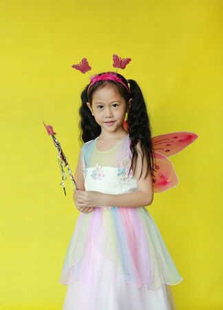 Pretty asian girl dressed in fairy costume with looking camera isolated on yellow background
