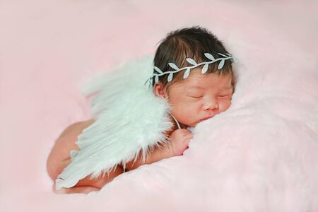 Portrait adorable of little newborn baby wearing angel costume and white wings, sleeping on fluffy soft fabric