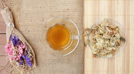 Chrysanthemum juice with dried Chrysanthemum flower on sack and wood mat. Top view