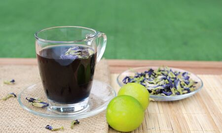 Juice of Butterfly pea in glass on wooden table with dried pea flowers and lemon. Herb drink