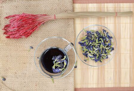 Juice of Butterfly pea in glass on wooden table with dried pea flowers. Herb drink. Top view.
