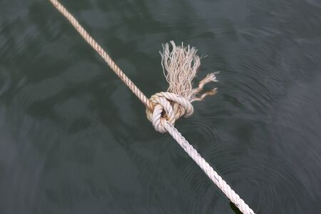Close up a Ship rope knot in a water.