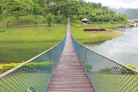 Wooden rope suspension bridge for walk crossing river.