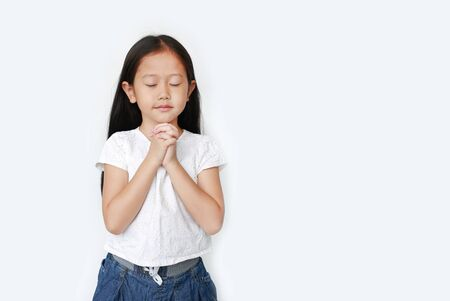 Close eyes beautiful little asian child girl praying isolated on white background with copy space. Spirituality and religion concept.