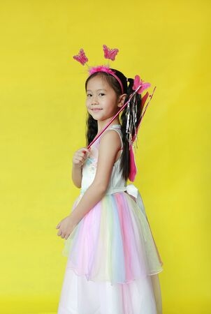 Beautiful asian little child girl dressed in fairy costume isolated on yellow background.
