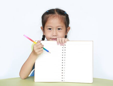 Portrait of little girl in school uniform show writing on blank notebook sitting at desk over white background. Stock fotó