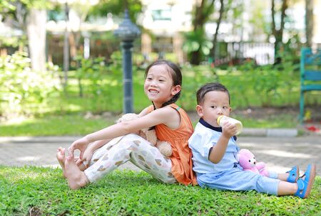 Happy little Asian sister and her younger brother sit back and lean back together in the green garden. Child girl cuddle teddy bear doll and boy Suck milk from bottle.