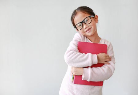 Asian schoolgirl wearing eyeglass hug a book and holding pencil in hand against white background with copy space. Portraits of child girl looking straight at camera.
