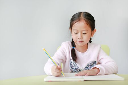 Portraits of little Asian child girl write in a book or notebook with pencil sitting on kid chair and table against white background. Standard-Bild