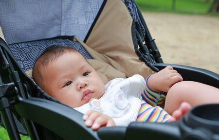 Close-up little Asian baby boy sitting in the stroller at the green garden.