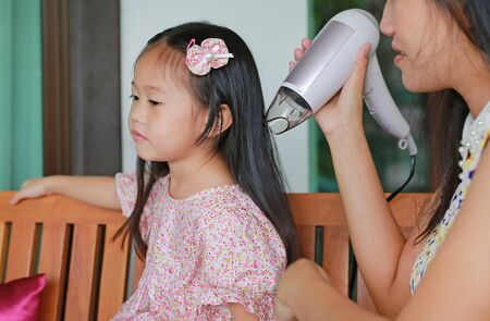 baby care after bathing, mother is combing daughter's hair Stockfoto