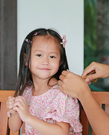 Mother is combing daughter's hair after bathing.